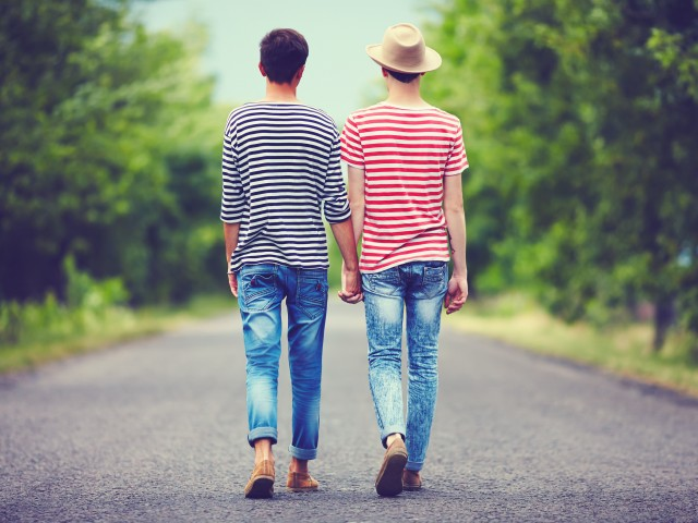 gay couple walking away together on spring road